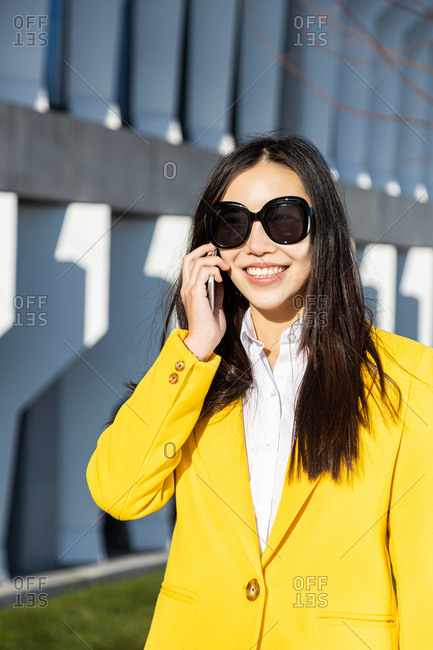 Smiling Asian business woman with yellow coat talking on phone with building in the background
