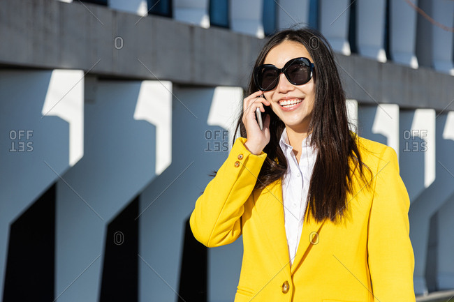 Smiling Asian business woman with bright yellow coat talking on phone with building in the background