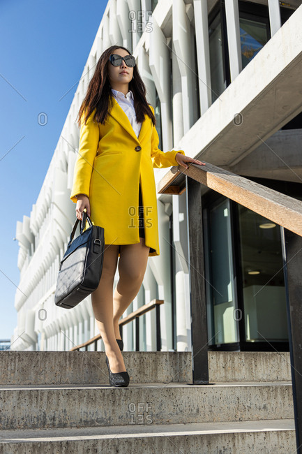 Asian business woman with yellow coat and smart phone walking down steps with building in the background
