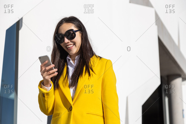 Smiling Asian business woman with yellow coat using cell phone with building in the background