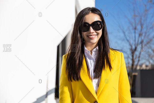 Smiling Asian business woman with yellow coat on city street with building in the background