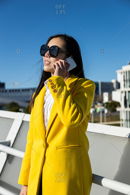 Asian business woman with yellow coat talking on phone with city in the background
