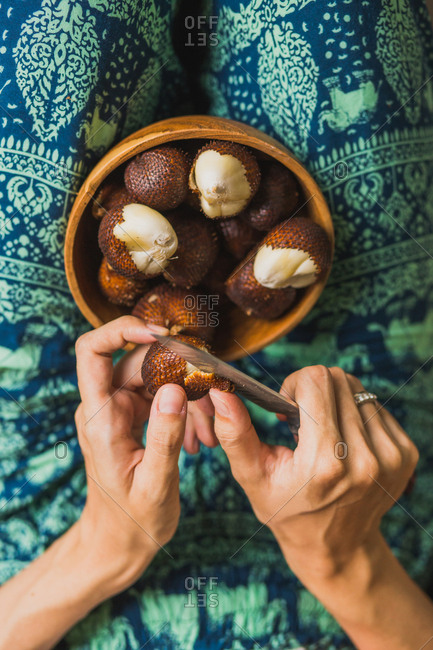 Overhead view of woman cutting snake fruit