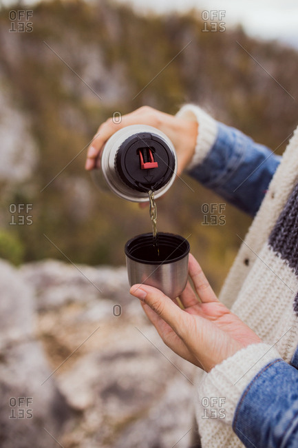 Woman pouring cup of tea from insulated mug
