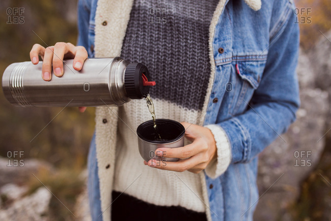 Close up of woman pouring cup of tea from insulated mug