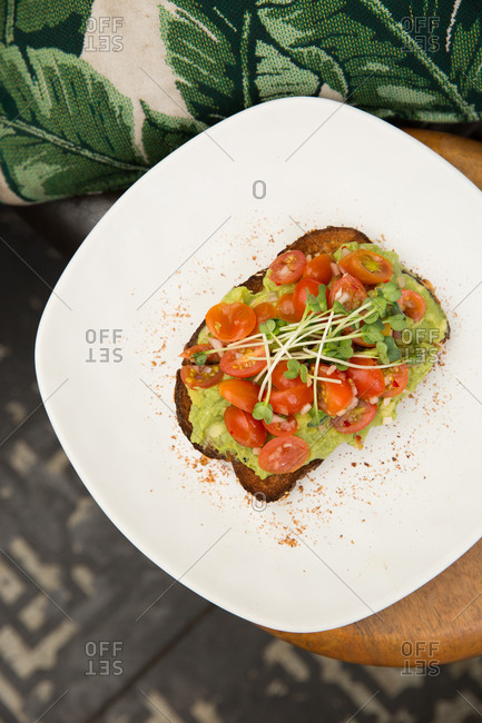 Avocado toast with tomatoes on a plate from above