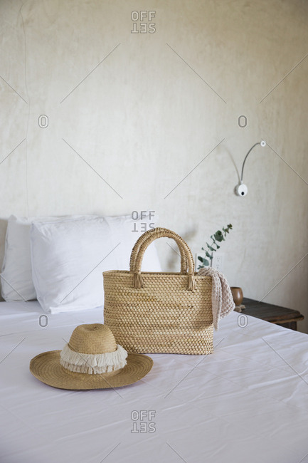 Stylish wicker bag and sun hat on a bed