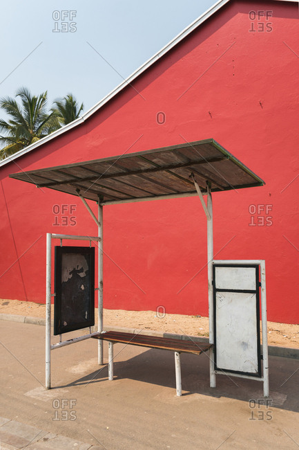 Empty bus stop with red background and palm trees in Morondava, Madagascar