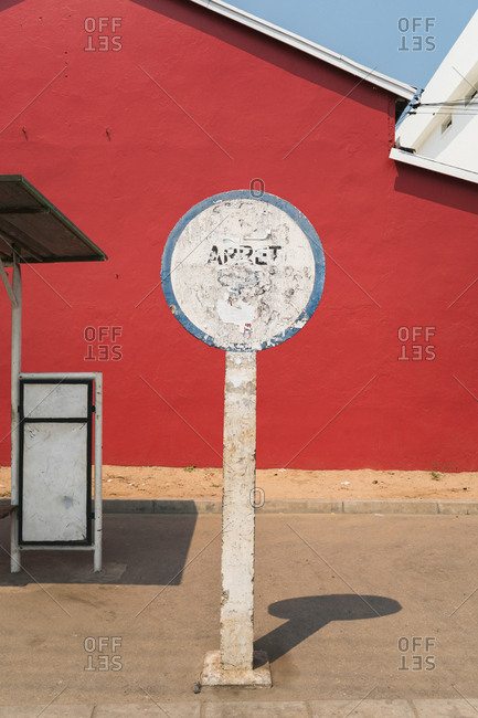 Weathered sign at an empty bus stop with red background in Morondava, Madagascar