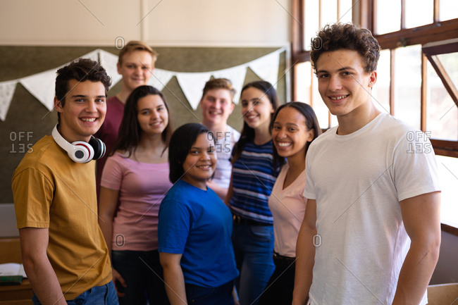 Front view of a multi-ethnic group of teenage school pupils standing together in a classroom and smiling to camera at break time