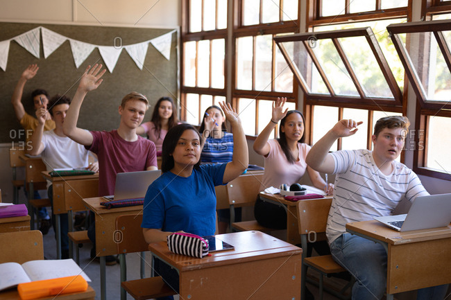 Front view of a multi-ethnic group of teenage school pupils sitting at desks in a classroom and raising their hands