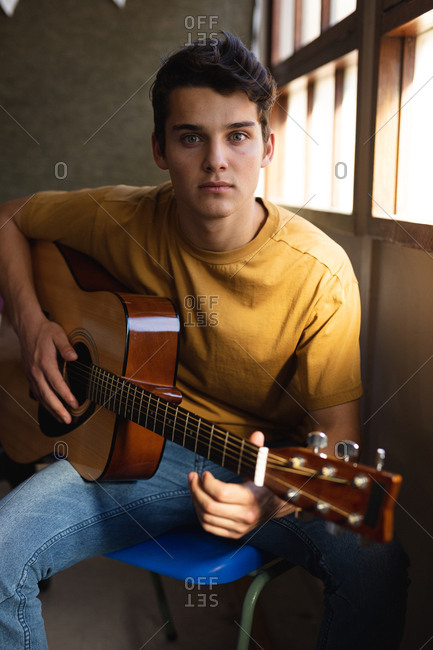 Portrait close up of a Caucasian teenage boy sitting by a window holding an acoustic guitar and looking to camera