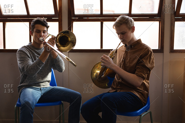 Front view of two Caucasian teenage boys sitting in front of a window playing a trombone and a French horn