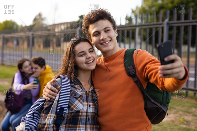Front view of a Caucasian teenage girl and boy embracing and smiling while the boy takes a selfie of them with a smartphone in their school grounds, another teenage couple sitting in the background