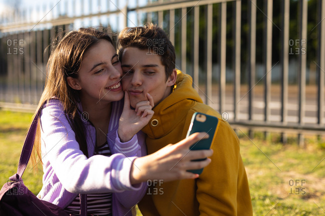 Front view of a Caucasian teenage girl and boy embracing and smiling, the girl squeezing the face of the boy while she takes a selfie of them with a smartphone in their school grounds, another teenage couple sitting in the background