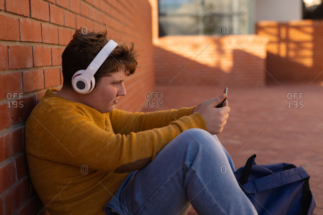 Side view close up of a Caucasian teenage boy sitting alone in a schoolyard wearing headphones and looking at a smartphone