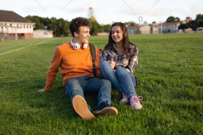 Front view of a Caucasian teenage girl and boy smiling at each other and holding hands, sitting in a school playing field