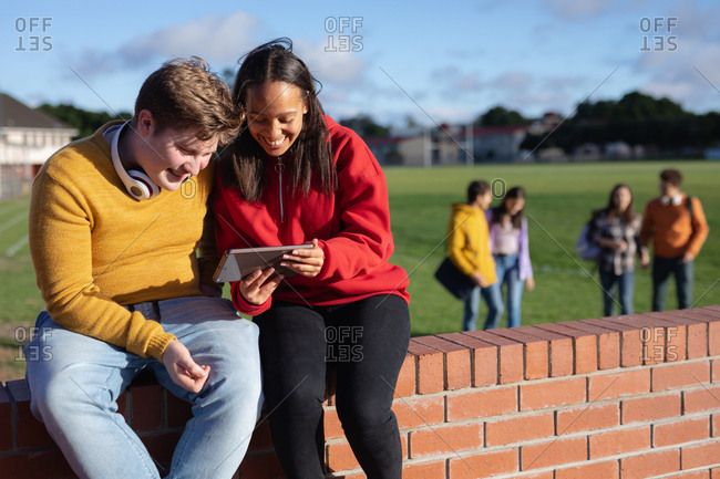 Front view of a Caucasian teenage boy and a mixed race teenage girl sitting on a wall looking at a tablet computer together and smiling, in a school playing field with two teenage couple walking in the background