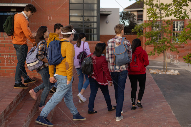 Rear view of a multi-ethnic group of male and female teenage students talking as they walk through their school grounds