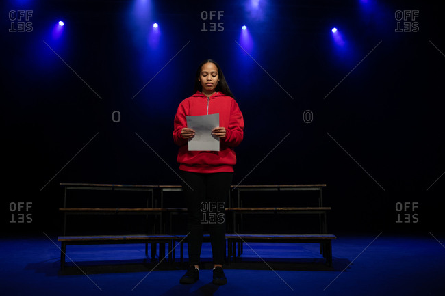 Front view of a mixed race teenage girl standing on stage holding a script in an empty school theatre during rehearsals for a performance