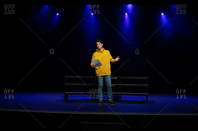 Front view of a Caucasian teenage boy standing on stage holding a script in an empty school theatre during rehearsals for a performance