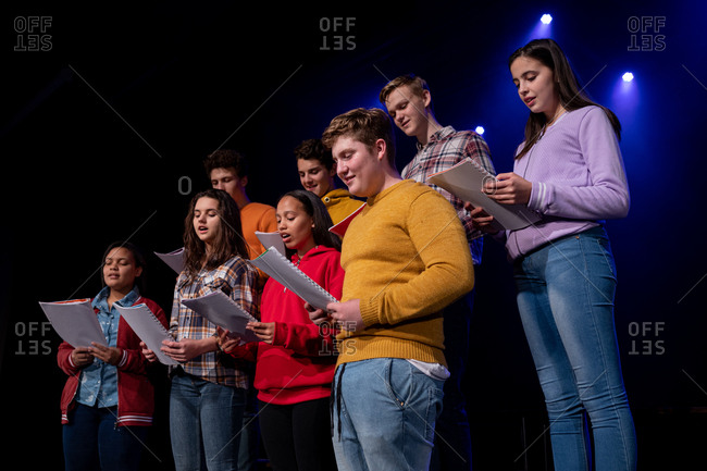 Side view close up of a multi-ethnic group of teenage male and female choristers holding sheet music and singing standing on the stage of a school theatre during rehearsals for a performance