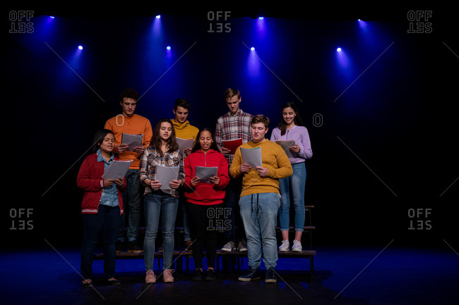 Front view of a multi-ethnic group of teenage male and female choristers holding sheet music and singing standing on the stage of a school theatre during rehearsals for a performance