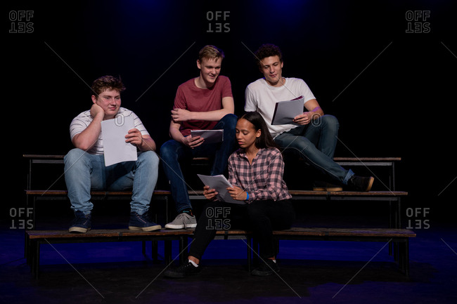 Front view of three Caucasian teenage boys and a mixed race teenage girl holding scripts and smiling, sitting on the stage of a school theatre during rehearsals for a performance