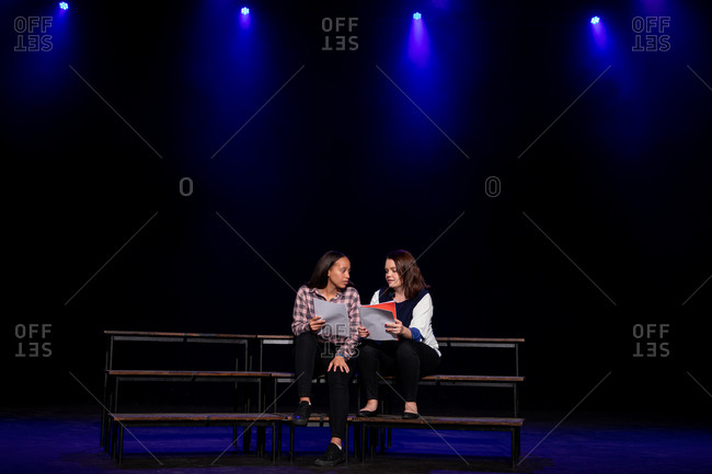 Front view of a Caucasian and a mixed race teenage girl holding scripts sitting on the stage of a school theatre during rehearsals for a performance