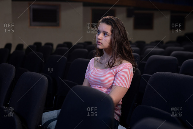 Front view of a Caucasian teenage girl sitting in the empty auditorium of a school theatre watching her friends on stage during rehearsals for a performance