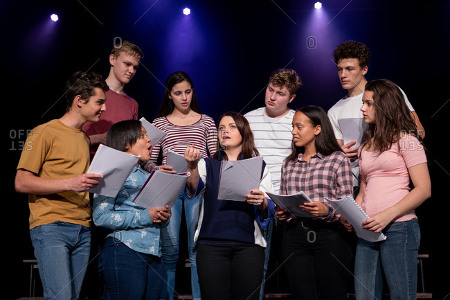 Front view close up of a multi-ethnic group of teenage male and female choristers holding sheet music and singing standing on the stage of a school theatre during rehearsals for a performance