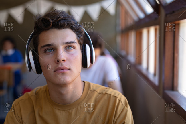 Portrait close up of a Caucasian teenage boy with dark hair and grey eyes sitting at a desk in a school classroom wearing headphones and looking at of a window