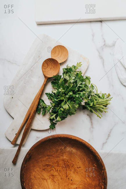 Overhead view of parsley beside a wooden bowl and spoons
