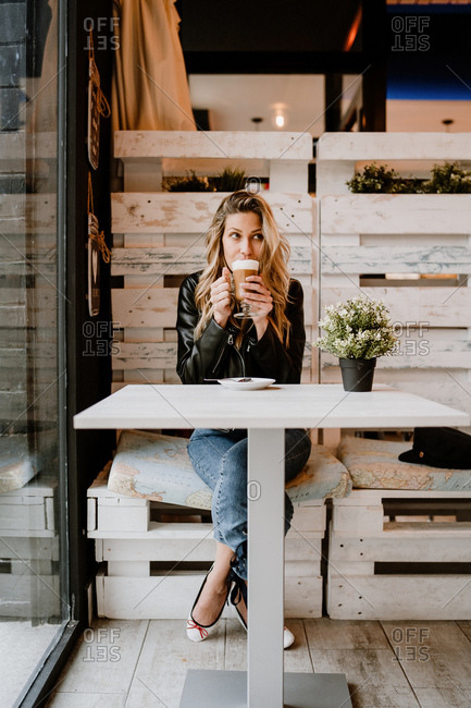 Long haired trendy beautiful blonde woman drinking from a glass of delicious foamy coffee while looking away