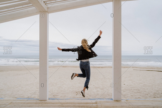 Back view of trendy unrecognizable woman in black jacket merrily jumping with arms raised on white wooden pier with ocean on background