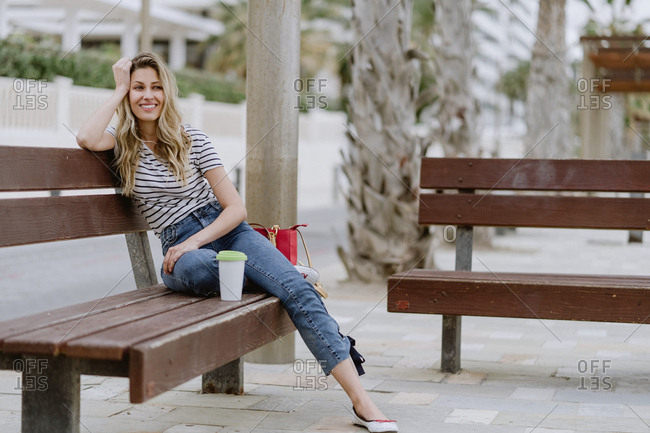Side view of cheerful casual young female sitting on city bench at seafront on summer day looking away