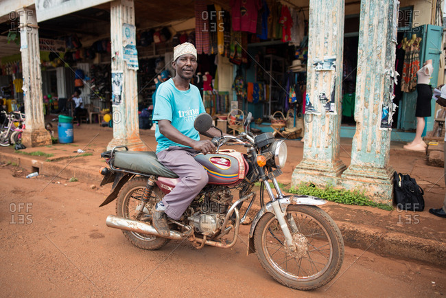 September 30, 2016: Jinja, Uganda September. 30:relaxed African American man in blue t-shirt riding old motorbike along dirty street with shops and looking at camera