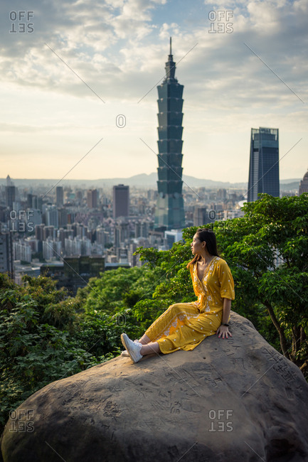 Tranquil female traveler in stylish yellow dress sitting in big rock while enjoying in views with city plants and sky on background in Scotland