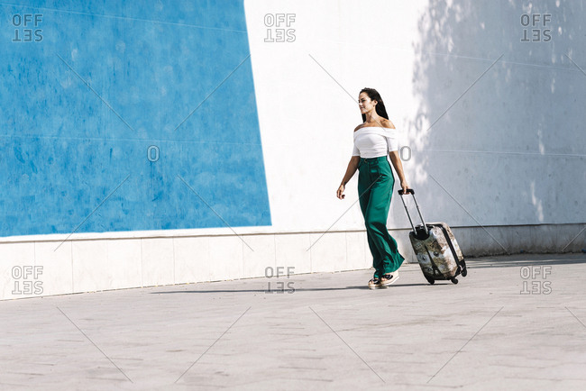 Side view of young female tourist carrying a baggage while walking in street
