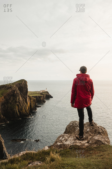 Lonely tourist standing on rocky coast against tranquil sea water under gray sky