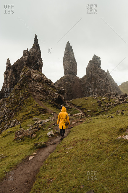High angle back view of person in bright yellow coat walking alone along footpath on green grassed hill against blurred misty rock formation Old Man Of Storr in Scotland