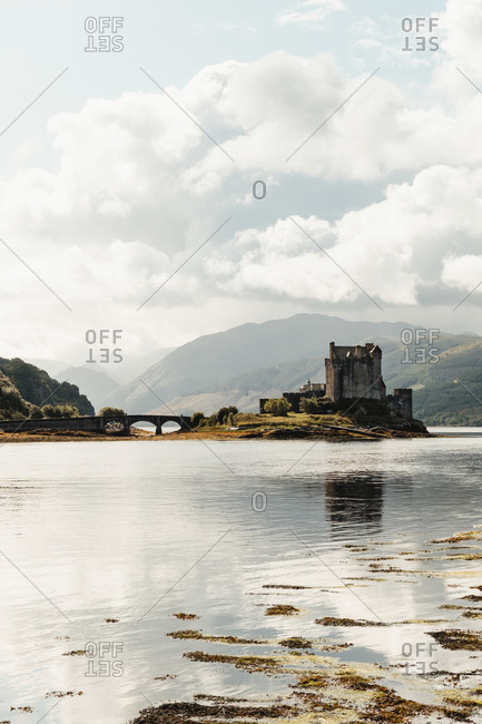 Wonderful scenery of abandoned medieval castle surrounded by river against foggy valley under blue sky with lush white clouds in Scotland