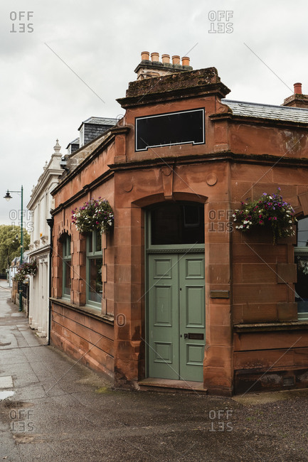 August 16, 2019: Vintage architecture red brick building with light green door and empty space for shop sign decorated with flowers on street of Scotland on cloudy day
