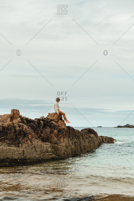 Lonely tourist sitting on rocky coast against tranquil sea water under gray sky