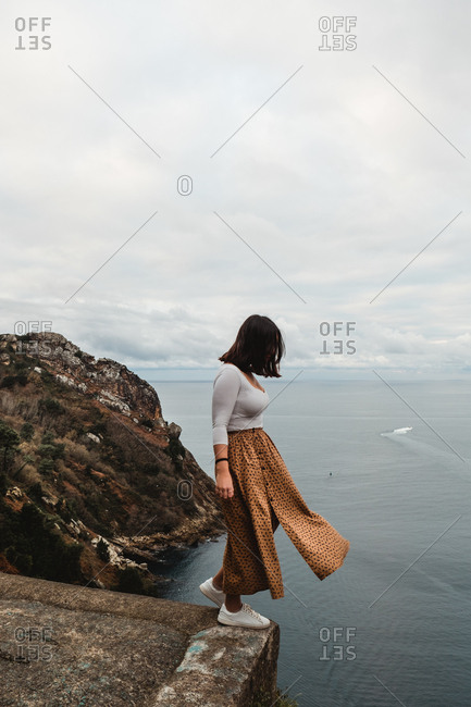 Side view of pensive solitary lady in casual clothes balancing on cliff edge and looking away against blurred rocky hill and tranquil ocean water in windy overcast weather