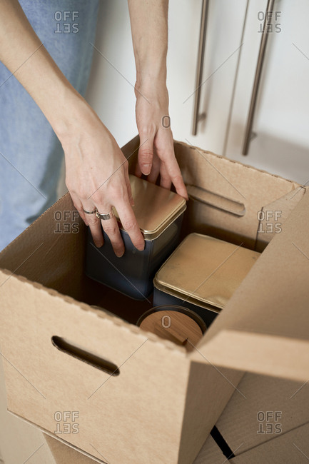 Unrecognizable cropped woman hands holding metal containers out of carton box