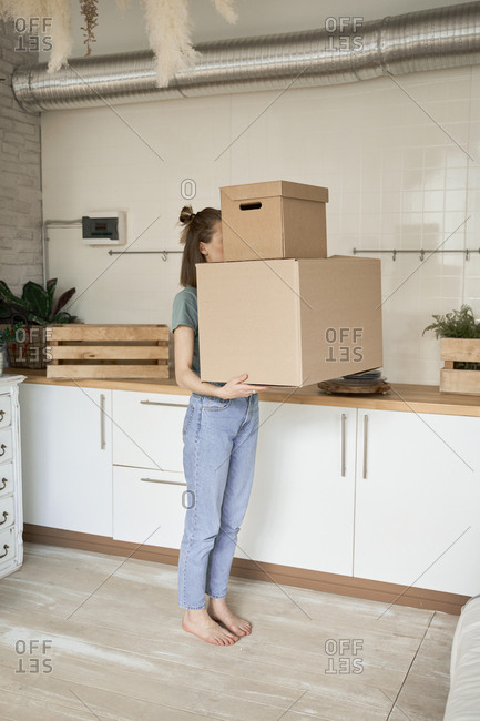 Side view of anonymous young woman making effort and carrying cardboard boxes with stuff in house