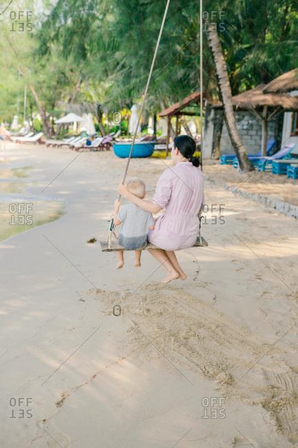 Joyful kid swinging with mother against blurred seascape