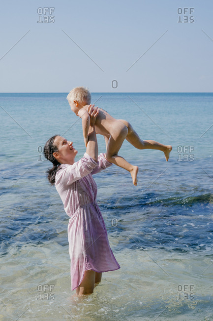 Woman and small kid having fun with water while relaxing on seacoast at resort