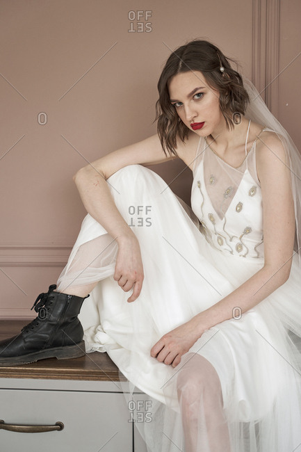 Attractive adult confident lady in white dress and military black shoes looking at camera